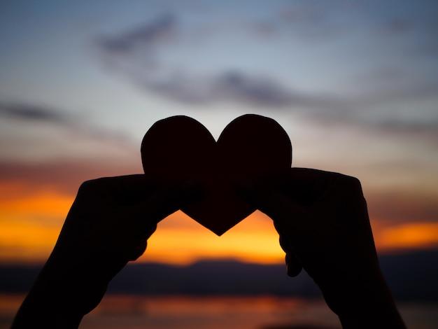 La mano della siluetta sta alzando il cuore di carta rosso con luce solare della sfuocatura durante il tramonto