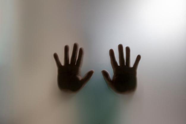 Sagoma di mani dietro il vetro smerigliato concetto di chiedere aiuto e violenza domestica