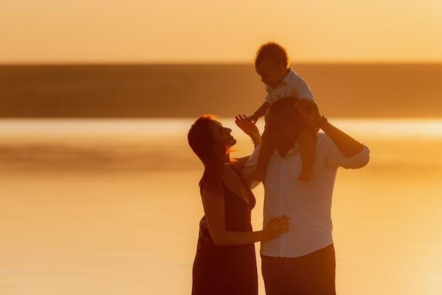 Siluetta della famiglia felice in spiaggia in una bella giornata estiva. famiglie che camminano la sera