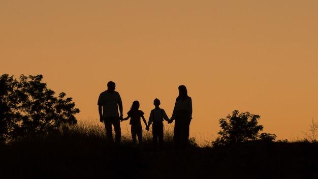 Silhouette di una famiglia di quattro felice, madre, padre, figlia, figlio al tramonto