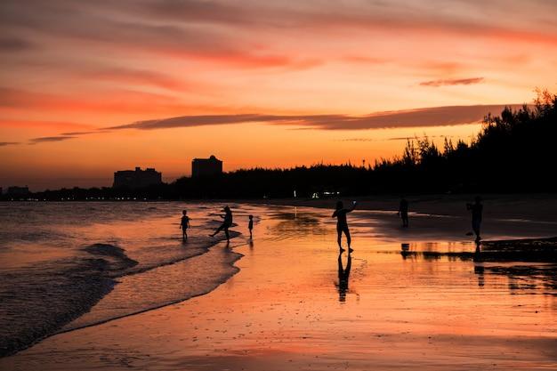 Silhouette famiglia felice che ha attività sulla spiaggia al tramonto a cha-am, phetchaburi, thailandia.