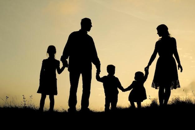 Siluetta di una famiglia felice con bambini sulla natura