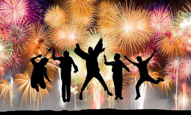 Silhouette di persone felici che saltano sui fuochi d'artificio, concetto di divertimento, successo e indipendenza
