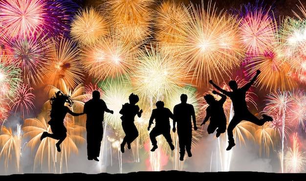 Silhouette di persone felici che saltano sui fuochi d'artificio, concetto di divertimento e successo
