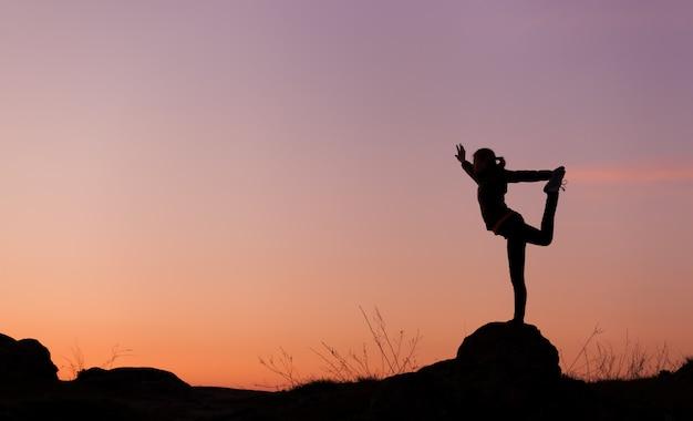 Siluetta di giovane donna felice contro il cielo al tramonto