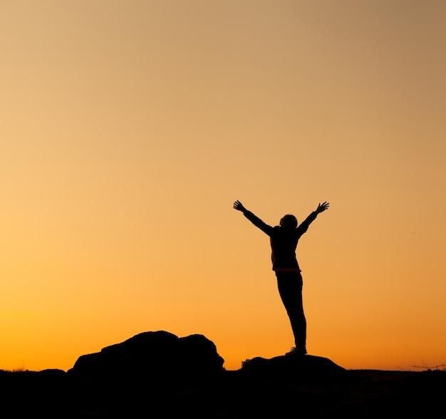 Silhouette di felice giovane donna con le braccia alzate contro il bellissimo cielo colorato. tramonto estivo. paesaggio