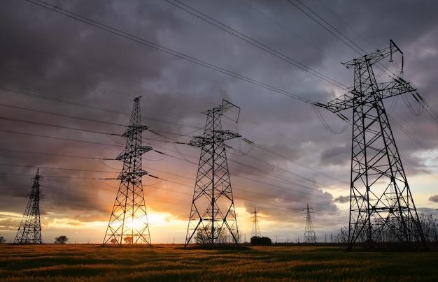 Silhouette torri elettriche ad alta tensione al tramonto. linee elettriche ad alta tensione. stazione di distribuzione di elettricità