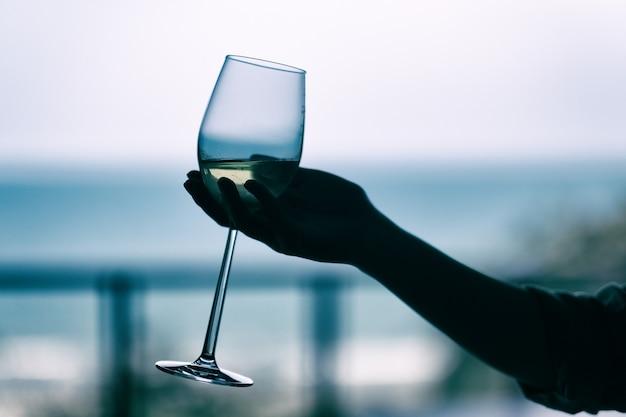 Immagine della sagoma della mano di una donna che tiene un bicchiere di vino con sfondo sfocato del mare