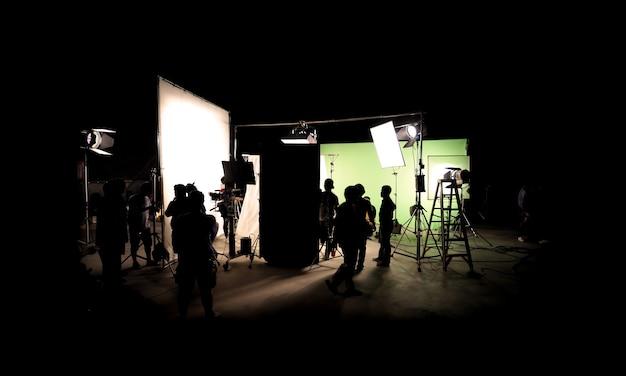 Immagini della sagoma della produzione video dietro le quinte o del b-roll o della realizzazione di un film commerciale per la tv che la troupe del team lightman e il cameraman lavorano insieme al regista in studio con l'attrezzatura