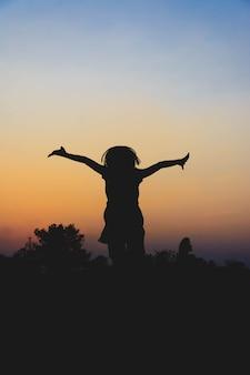 Silhouette di bambini che corrono e godono in mezzo al campo di riso al tramonto