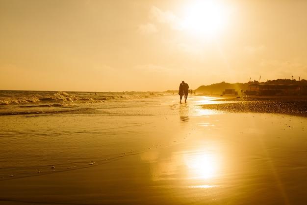 Silhouette di una coppia di innamorati che cammina lungo una spiaggia sabbiosa e si gode il tramonto