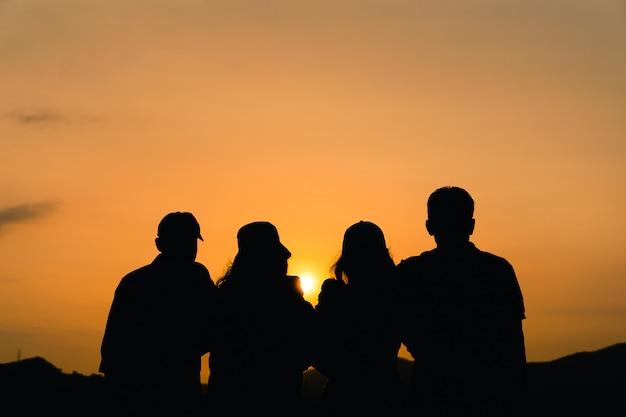 Siluetta degli amici maschii e femminili che si abbracciano che esamina l'alba. felicità, successo, amicizia e concetti di comunità.