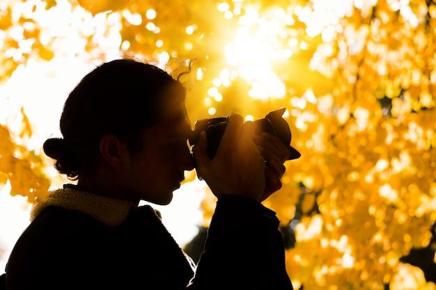 Sagoma di un fotografo maschio sotto un albero in autunno con foglie gialle luminose