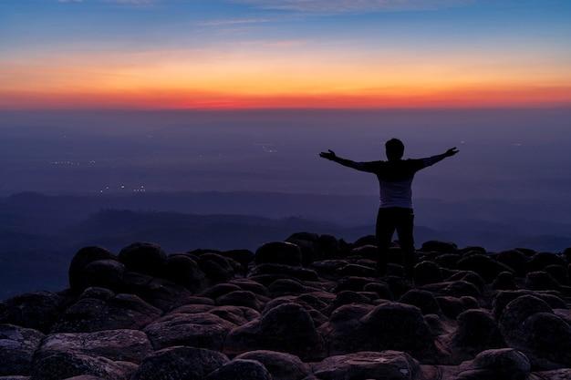 Silhouette uomo nella parte posteriore con le braccia aperte in piedi sul punto di vista al picco di montagna di pietre nodulari o lan hin poom durante il tramonto, parco nazionale di phu hin rong kla a phitsanulok, thailandia, concetto di libertà