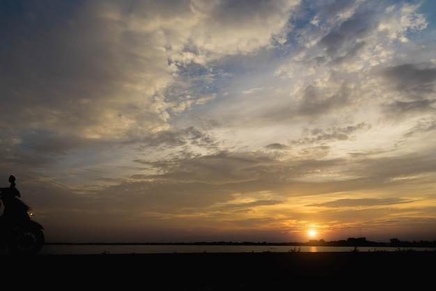 Siluetta di una motocicletta motociclista uomo al tramonto