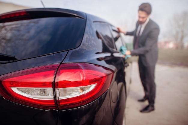 Sagoma di uomo in abiti eleganti, lucidando la sua auto.