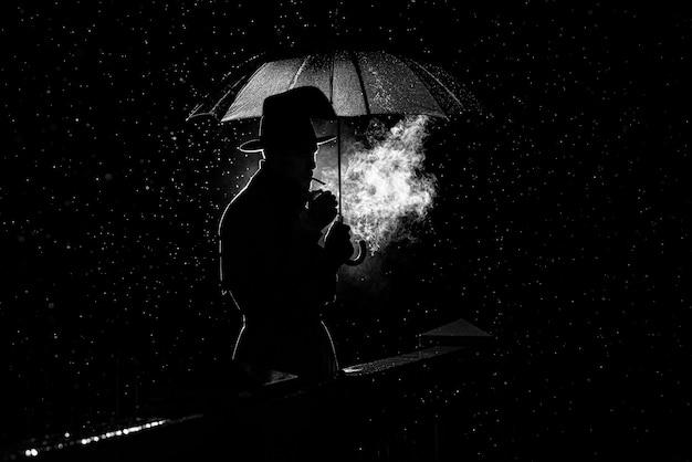 Sagoma di un uomo con un cappello sotto un ombrello fumare una sigaretta di notte sotto la pioggia nel vecchio stile noir crimine