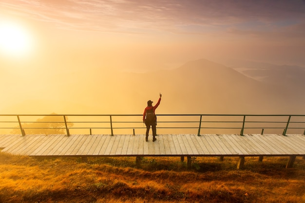 Sagoma di uomo tenere le mani sulla cima della montagna, concetto di successo