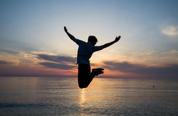 L'uomo della siluetta sta saltando alla spiaggia sulla vacanza crepuscolare del fondo del mare.