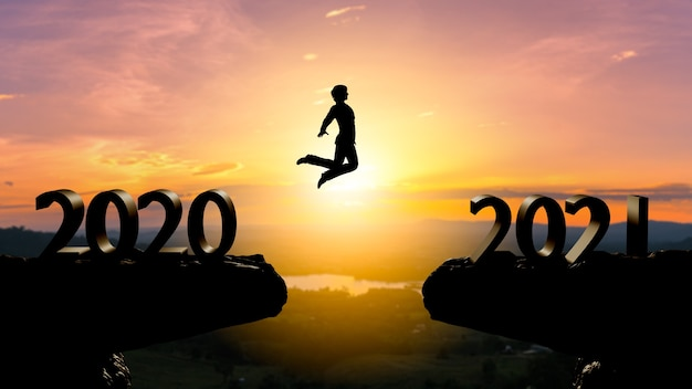 Silhouette uomo salta tra il 2020 e il 2021 anni con il muro del tramonto, concetto anno 2021