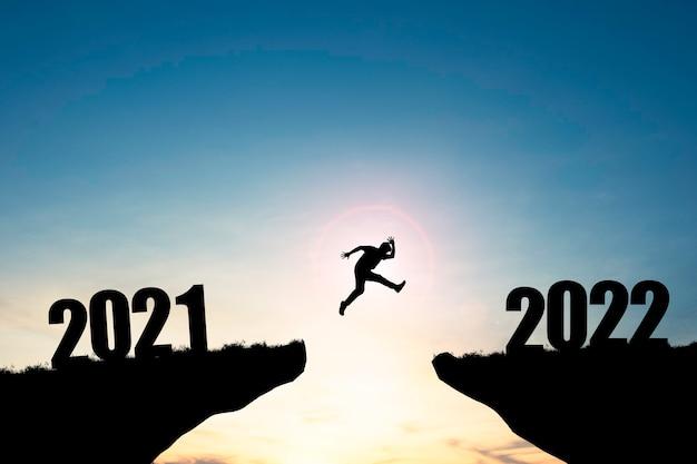 Silhouette uomo che salta dalla scogliera del 2021 alla scogliera del 2022 con cielo blu e luce solare, preparazione di un nuovo obiettivo aziendale di sfida e vita per il nuovo anno.