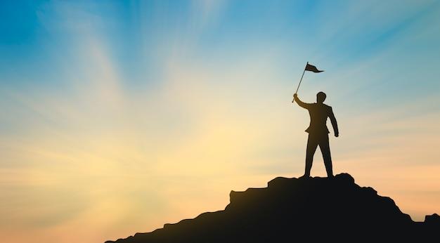 La siluetta dell'uomo sulla cima della montagna sopra luce del sole e del cielo, successo di affari, direzione, risultato e concetto della gente