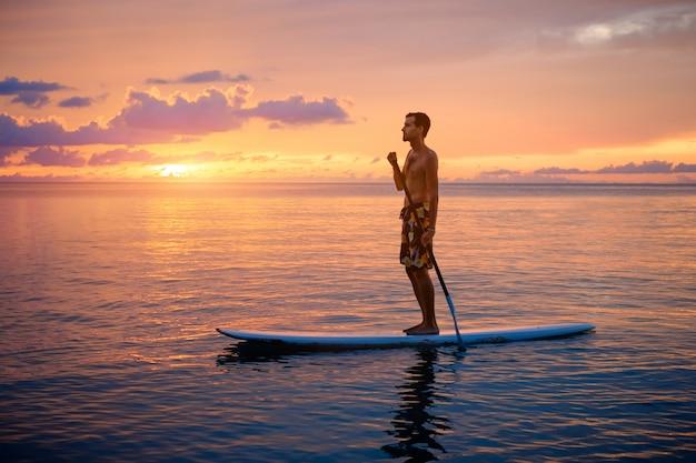 Siluetta dell'uomo che paddleboarding al tramonto