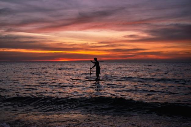 Sagoma uomo pagaia sub board sul mare e cielo colorato al tramonto