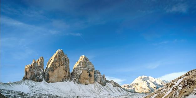 Siluetta dell'uomo sulla cima della montagna sul cielo di alba, sullo sport e sulla vita attiva concettuali.