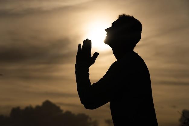 La siluetta dell'uomo prega durante il tramonto. pentimento, rimpianto e concetto di speranza.