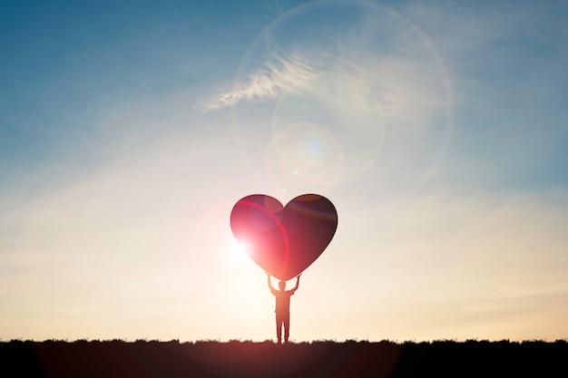 L'uomo della siluetta mostra due mani che si alzano e portano il cuore con la luce del sole e il cielo blu, concetto di san valentino.