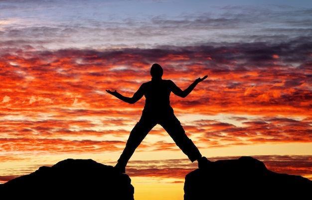 Siluetta dell'uomo sullo sfondo del cielo infuocato al tramonto