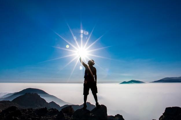 Silhouette di un uomo che tocca il sole con una mano in cima a una montagna
