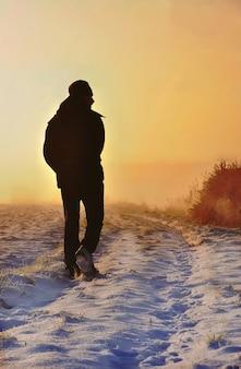 Sagoma di un uomo al crepuscolo che cammina in un sentiero innevato in campagna