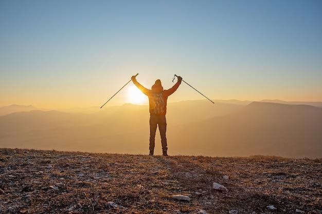 Una silhouette di un uomo con uno zaino e bastoncini da nordic walking si erge sulla cima di una montagna con le mani alzate