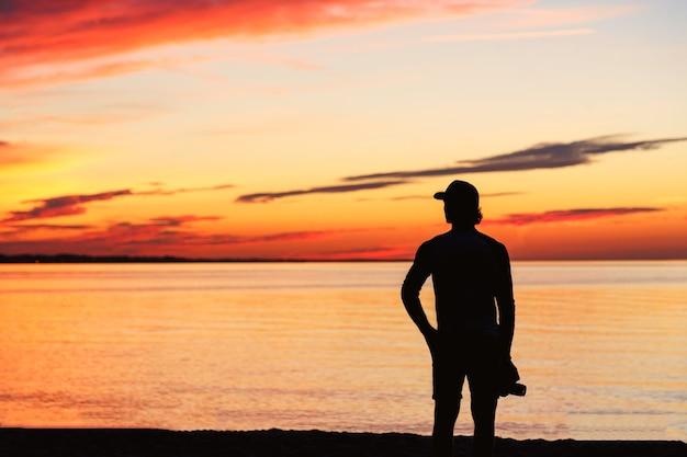 Sagoma di uomo con la fotocamera e bellissimo tramonto arancione