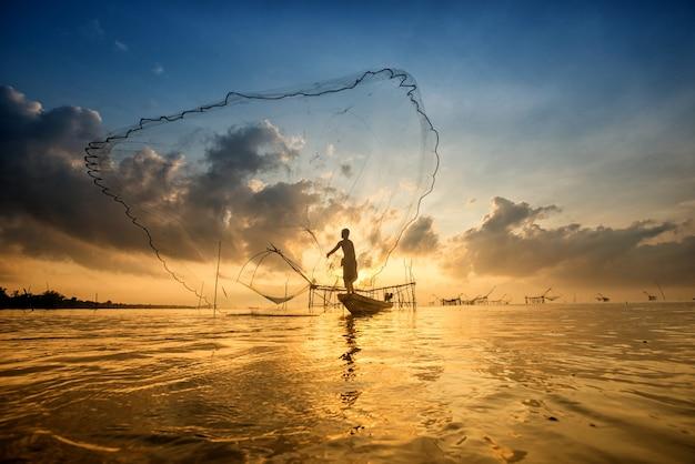 Silhouette di uomo con reti da pesca in mattinata a pakpra, phatthalung, thailandia