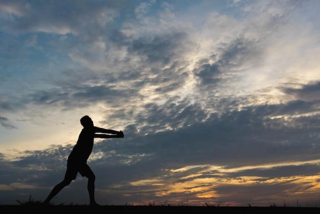 Siluetta di un uomo con l'uomo che si esercita al tramonto.