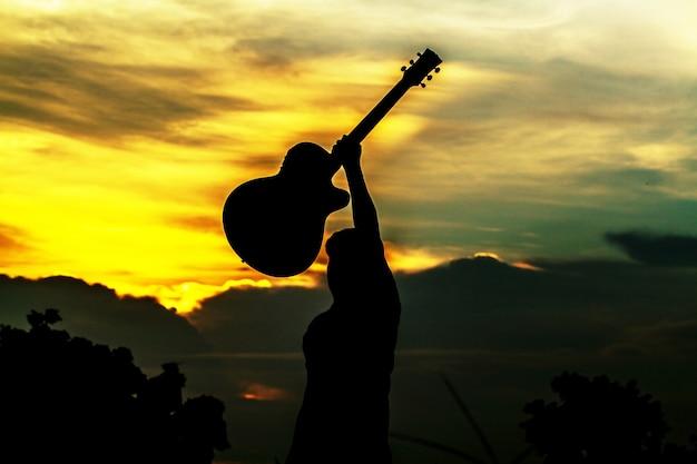 Silhouette di uomini hanno dimostrato che la felicità e il successo. e tenendo una chitarra in testa al tramonto.