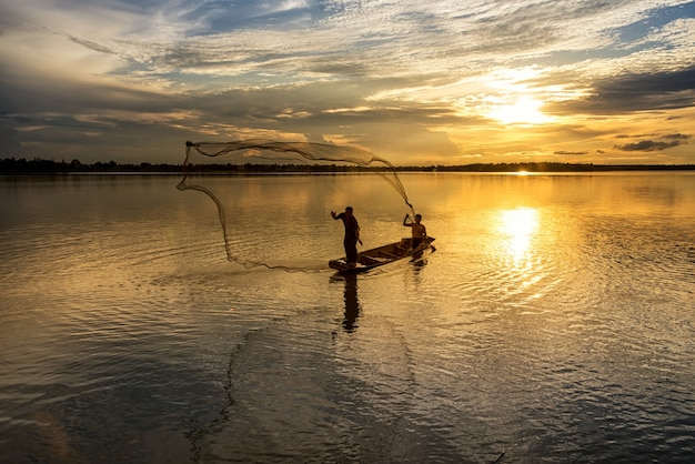 Silhouette di uomini con reti da pesca in wanonniwat, sakon nakhon, thailandia