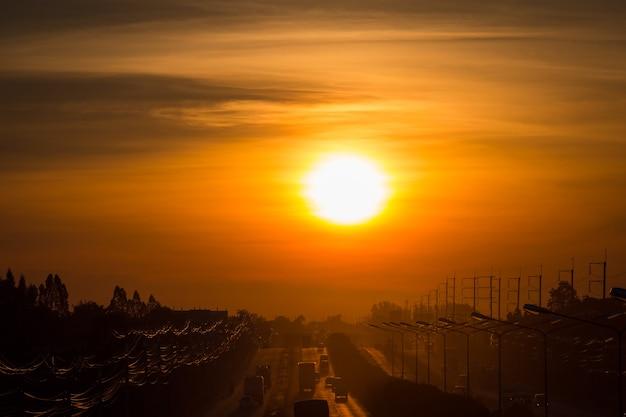 Profili il sole di mattina sulla strada con un impianto di perforazione e le linee elettriche.