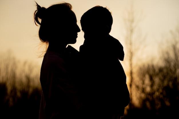 Siluetta di una madre e di un figlio che giocano all'aperto al tramonto. concetto di festa della mamma