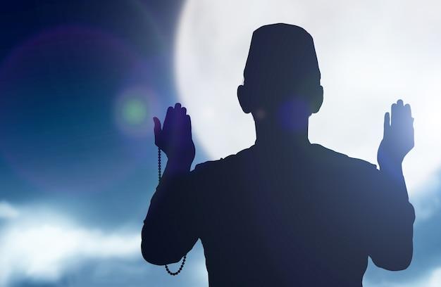 Siluetta dell'uomo musulmano che prega con i grani di preghiera sulle sue mani