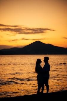 Silhouette di una coppia di sposini sulla scena del sole al tramonto