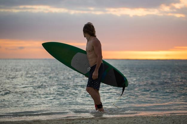 Surfista di bordo di pagaia della siluetta sul tramonto