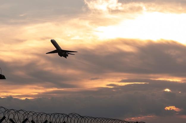 La siluetta di un aereo passeggeri che vola al tramonto decolla vicino all'aeroporto