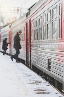 Silhouette di passeggeri entra nel treno in inverno all'aperto
