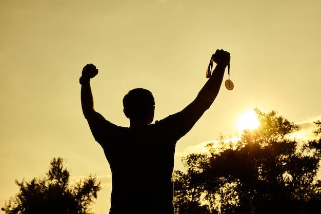 Silhouette persone vittoria alzando le mani e tenendo la medaglia d'oro con il cielo al tramonto.