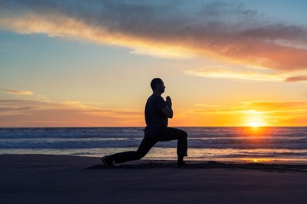 Silhouette di una persona sulla spiaggia che fa yoga o esercizio al bellissimo tramonto