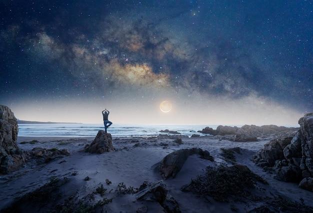 Siluetta di una persona nella posizione dell'albero di yoga su una roccia con la via lattea e la luna sullo sfondo